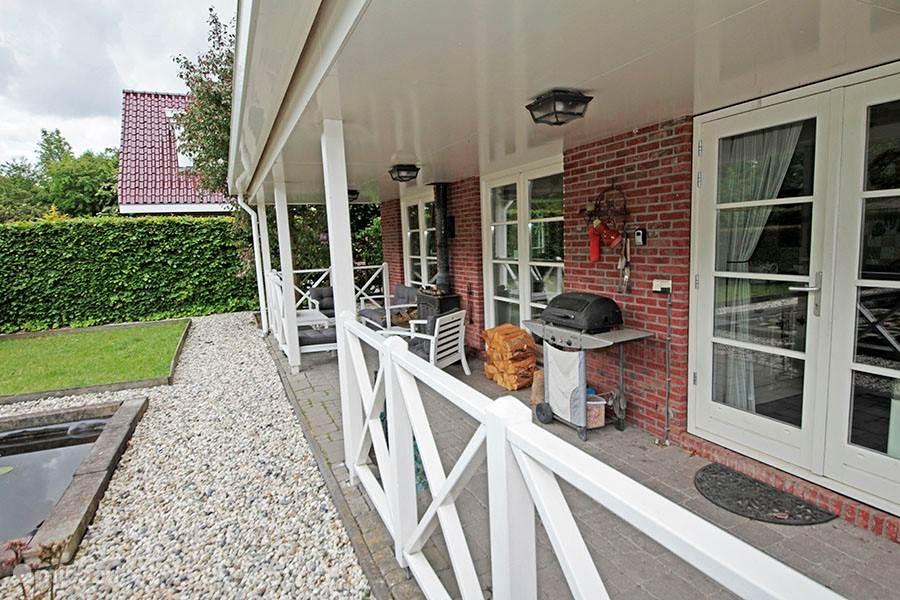 Achter het huis zit over de hele breedte de veranda. De BBQ staat tot uw beschikking.