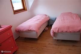 Een van de kamers met 2 losse bedden en een vrolijke oude commode!