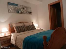 slaapkamer met dubbel bed, badkamer met douche/lavabo en toilet