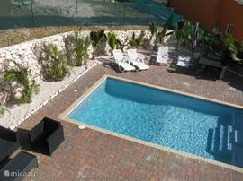 a lovely swimming pool with terrace around it with chairs, lounge chairs, table and chairs and umbrellas.