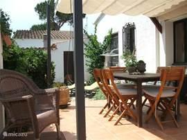 Eetgedeelte buiten waar u kunt zitten tot zonsondergang.  Dining area outside with sunshade.