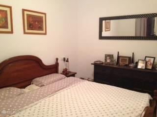 Tweepersoons slaapkamer met dressoir en spiegel.  Masterbedroom with dresser and mirror.