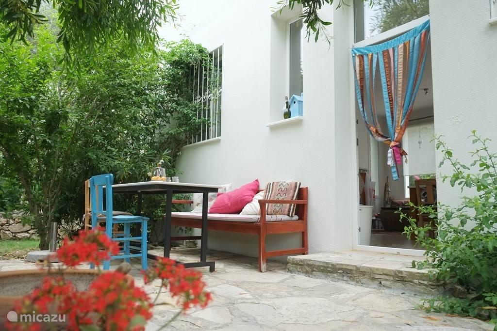 Het terras aan de voorkant, waar u, vooral als het warm is  heerlijk kunt ontbijten tussen de blauwe jasmijn en de bougainvillea.