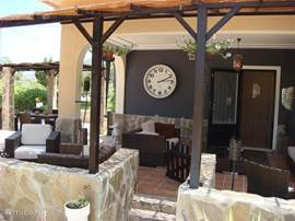 View of the lounge terrace with right behind that the outside dining table underneath the pergola.