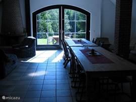 Woonkamer geeft toegang door de openslaande tuindeuren tot het terras en Meer.