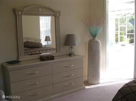 Meubel met grote spiegel in de masterbedroom, met deur naar terras. Bij de masterbedroom hoort ook een walk in closet!