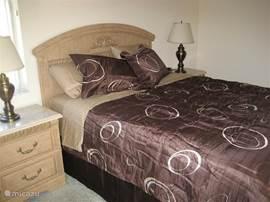 Slaapkamer aan de achterzijde van het huis met queensize bed + meubel met grote spiegel.   Slaapkamer heeft ingebouwde kledingkast