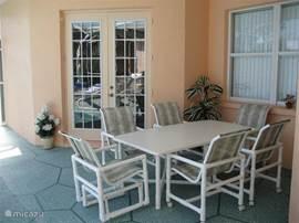 Eén van de 3 tuintafels met bijpassende stoelen. Op de achtergrond zijn de deuren van de masterbedroom te zien