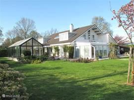 Zwembad hal met villa en tuinkamer en gezellige terrassen,  rondom de villa licht de tuin met vijvers