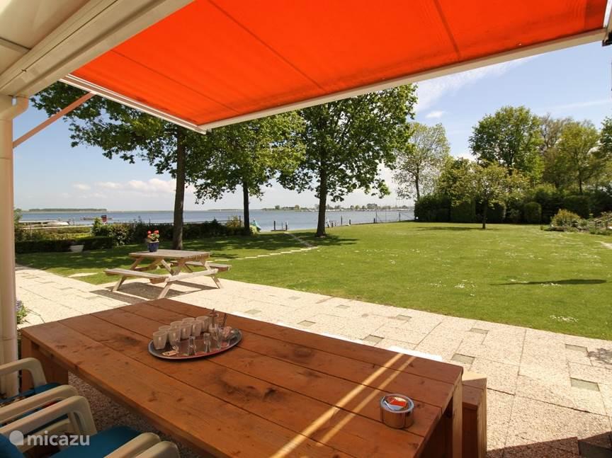 Een schitterend uitzicht van af het terras over de tuin en het Veerse Meer tijdens een lekker kopje koffie of thee dat de gastvrouw schenkt bij uw aankomst.