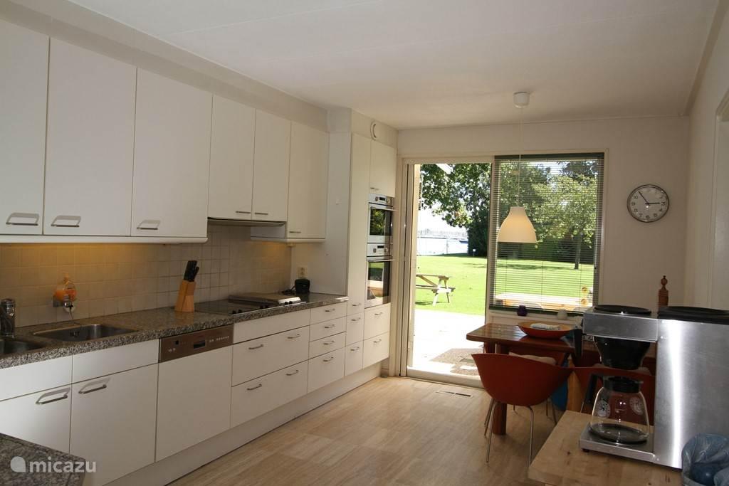 Keuken zeer volledig, moderne hete lucht oven, magnetron, vaatwasser, elektrische kookplaten, ingebouwde friteuse en een gezellige ontbijt hoek natuurstenen aanrecht en vloer  met zicht op de tuin en het water.