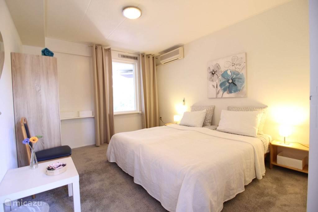 Begane grond slaapkamer met twee boxspring  bedden  en een airco