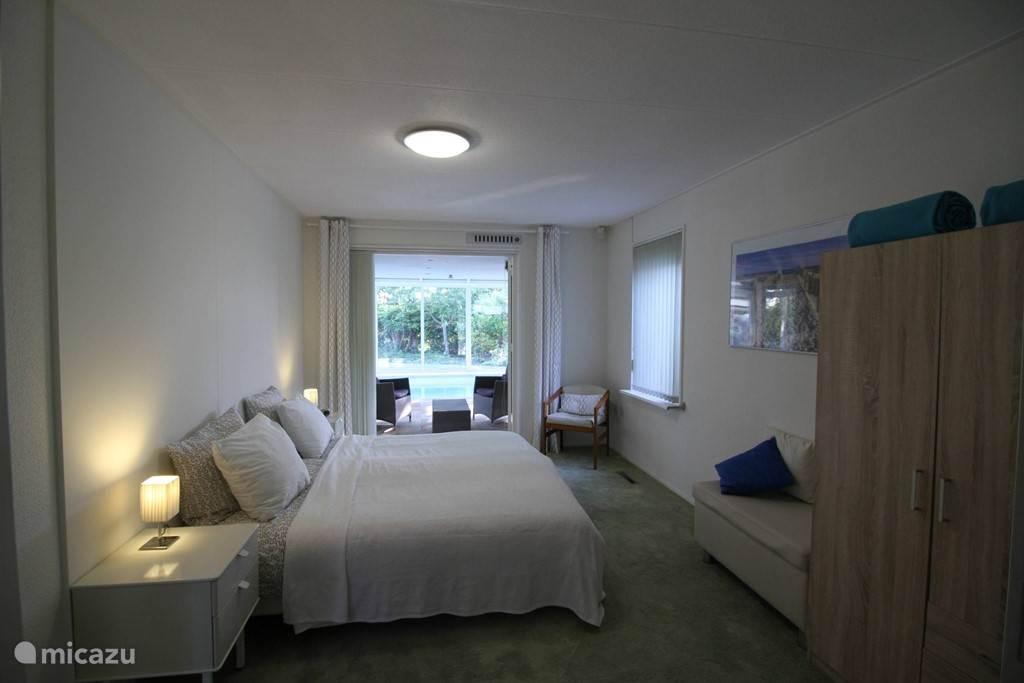 slaapkamer op de begane grond met openslaande deuren naar het zwembad, badkamer ensuite.