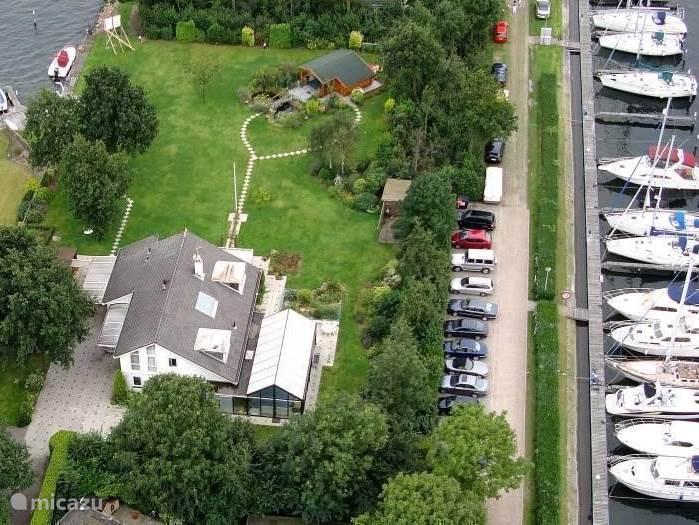 Omgeven door dichte bebossing met volledige privacy.ligt onze luxe vakantie villa De Veerse Hoek met met privé zwembad, rechts op de foto de jachthaven en links de eigen aanleg steigers en de walkant.