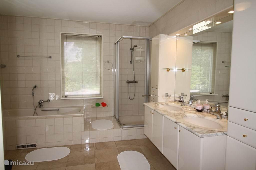 Luxe badkamer op de begane grond, badmeubel, douche ,ligbad, bidet, toilet en urinoir om je na een drukke dag in te ontspannen.
