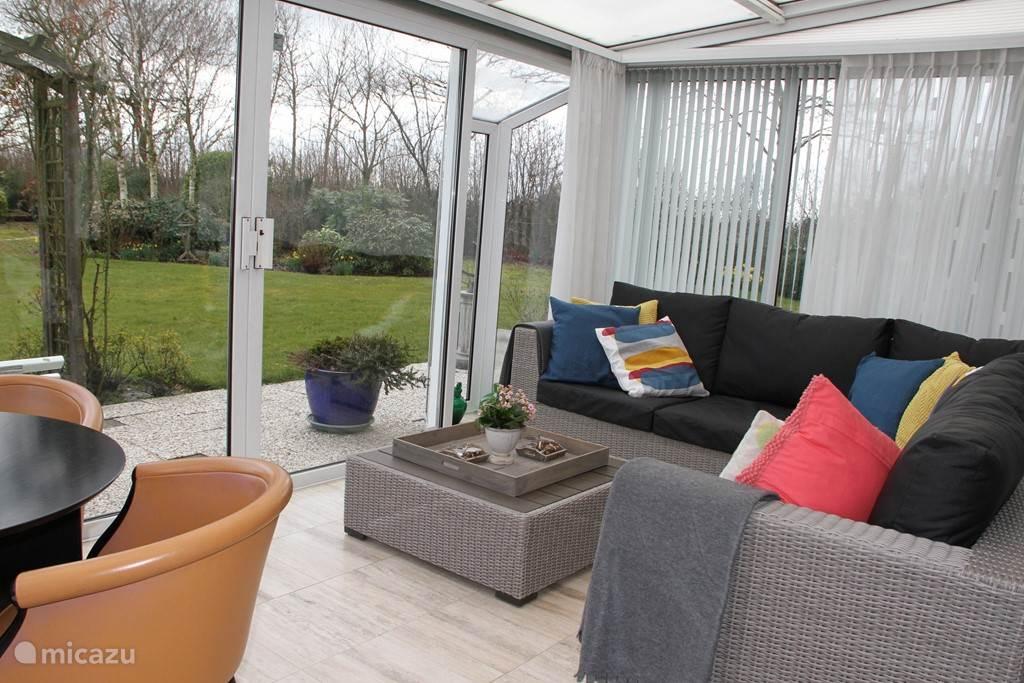 Gezellig lounge set in de tuinkamer om van de rust en het mooie uitzicht te genieten