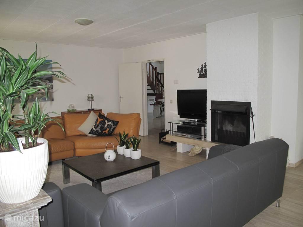 Woonkamer gezellig en comfortabel met  leer en leisteen tafel op een natuurstenen vloer, openhaard, flatscreen tv, audio dvd set.