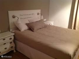 Tweepersoonsbed in de master bedroom met op het hoofdboard een tekst aar je in je vakantie oer nadenkt...