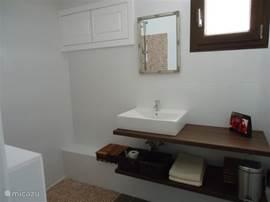 Badkamer en suite: Wastafel met voldoende ruimte voor het opbergen van je spullen