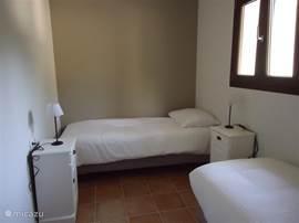 Kleine slaapkamer met 2 1 peroonsbedden. Deze kunnen ook aan weerskanten van de muren worden geplaatst zodat zij tegenover elkaar staan