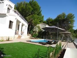 Het aanzicht van de woning vanaf het gras met het zwembad ervoor