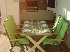 De eettafel staat al gedekt op de veranda, de TV kun je naar het terras draaien. BBQ op de achtergrond