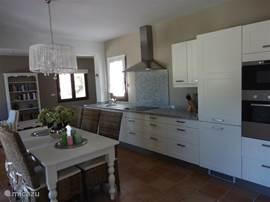De woonkeuken met 6 persoons eettafel en zeer compleet ingerichte keuken.