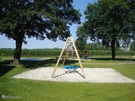 De kinderen kunnen zich heerlijk uitleven in de speeltuin met klimtoestel, luchtkussen en grote schommel.