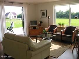 De woonkamer met openslaande deuren naar het terras en de tuin is hel licht met mooi uitzicht.