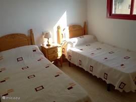 Dit is de tweede slaapkamer. Uiteraard is het mogelijk de bedden naast elkaar te schuiven voor een dubbelbed. Ieder slaapkamer heeft een eigen badkamer en grote inbouwkasten. De ramen hebben rolluiken.