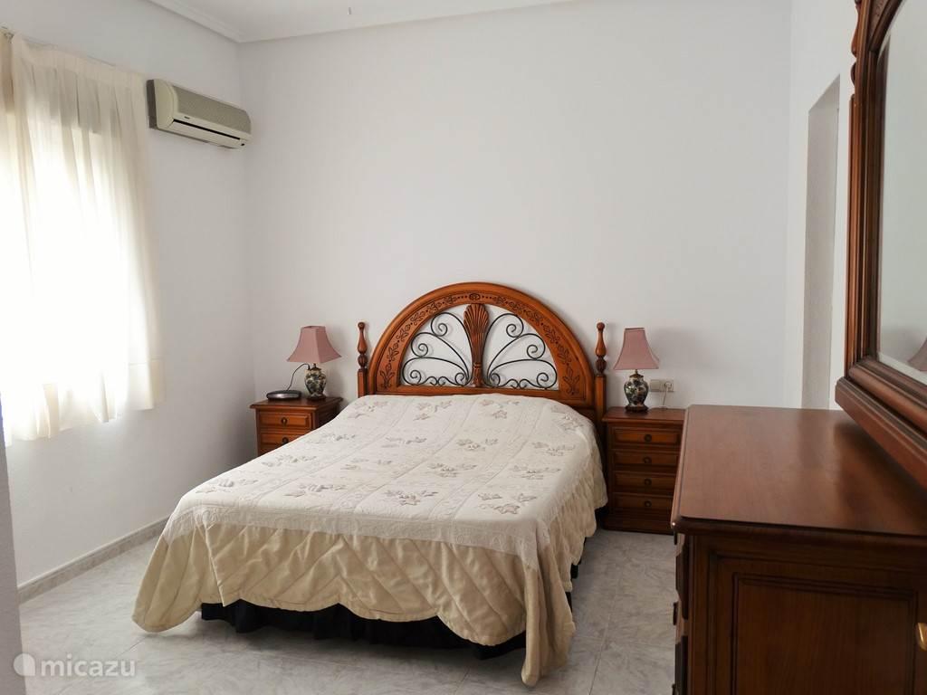 Grote slaapkamer met badkamer ensuite en airconditioning, nachtkastjes, ladenkast met spiegel, wekkerradio