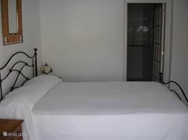 Slaapkamer met badkamer ensuite, uitzicht op het zwembad.