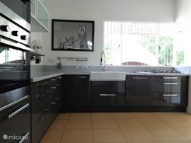 Grote open keuken die van alle luxe voorzien is (grote Amerikaanse koelkast met ijsblokjesmachine, vaatwasser, 5 pits gasfornuis, oven, magnetron, koffiezetapparaat, waterkoker, broodrooster etc.) en goed uitgerust is met hoogwaardig keukengerei.