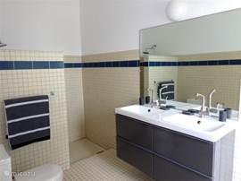 Badkamer 1. De Tropenvilla beschikt over drie badkamers. Alle badkamers zijn voorzien van regendouche, toilet, grote wastafelmeubels met spiegel, heerlijke dikke handdoeken en natuurlijk een föhn.