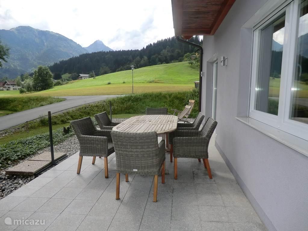 Het terras aan de voorzijde van het huis met uitzicht op de Alpen en de Pyreneeën. Het terrasmeubilair bestaat uit; 6 stoelen, 2 loungechairs, 2 zweefparasols en een grote tafel.