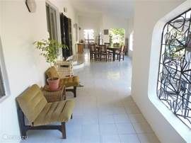 The spacious and cool verandah with a dining table for eight overlooks the terrace and garden. There is a high chair for the smallest children .