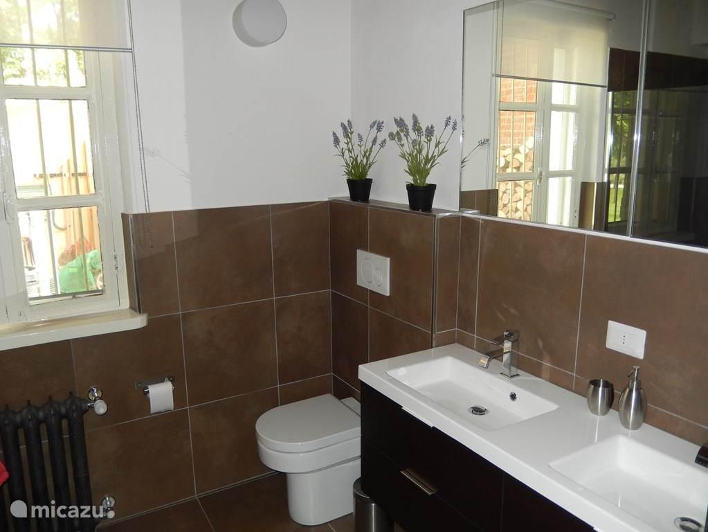 De nieuwe badkamer op de benedenverdieping van de villa. Met dubbele inloop douches: 2 regen- en 2 handdouches. Dubbele wastafel en toilet.