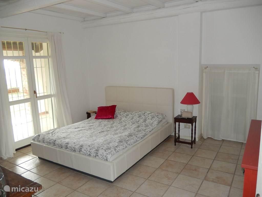 De master slaapkamer met toegang tot een gerieflijk balkon met spectaculair uitzicht. Uiteraard met een comfortabel 2-persoons-bed
