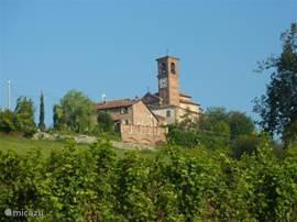 het huis gelegen op een heuveltop, naast een idyllisch 18e eeuws Romaans kerkje