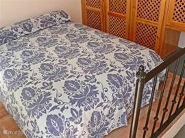 Tweede slaapkamer met tweepersoonsbed, grenzend aan het dakterras.
