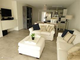 The spacious living room with open kitchen provides seating for at least 6 persons. In the living room there is also a flat-screen TV, DVD player and an amplifier for your iPod or iPhone.  The white benches in the picture have been replaced with a taupe sofa, pictures according shortly.