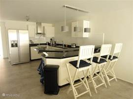 The spacious kitchen with breakfast bar is fully equipped.