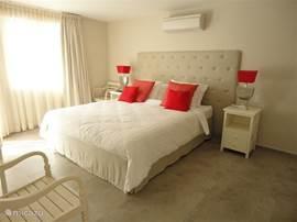Master Bedroom met airco, deur naar de porch, king size bed (1.80*2.20 cm), flatscreen televisie en DVD speler.