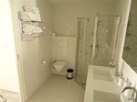 Badkamer, aangrenzend aan Master Bedroom met douche, toilet, dubbele wastafel, ligbad en hotelfohn.
