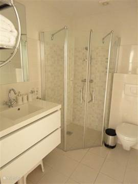 Bathroom, adjacent to Second Bedroom with shower, toilet, washbasin and hotelfohn.