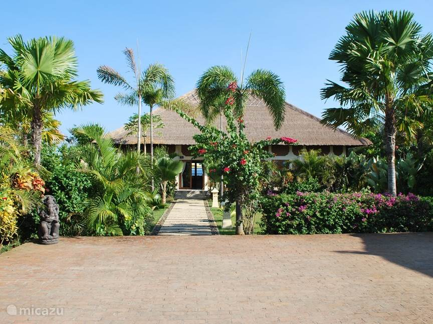 The front view from the parking lot with a part of the beautiful flowery garden (over 2000 m2) of Villa Cerah, Bali.