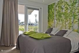 De slaapkamer heeft ook een schuifdeur. Hierdoor loop je gelijk op het grote terras met prachtig uitzicht.