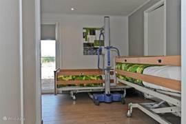 De 3e slaapkamer heeft 2 twee hoog/laag bedden. Hier is ook een mobile tillift aanwezig. Deze kan rechtstreeks naar de badkamer gereden worden.
