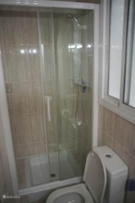 De tweede badkamer heeft een ruime douche, wastafel met opbergmeubel en toilet.