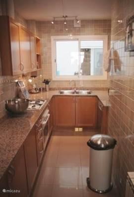 De volledig ingerichte keuken heeft een nieuwe koelkast met vriesvak, combimagnetron, oven, afwasmachine, blender, koffiezetapparaat en waterkoker. Ruim mooi servies, glaswerk, pannen, bestek en kookgerei aanwezig. De keuken kijkt uit op de loggia.